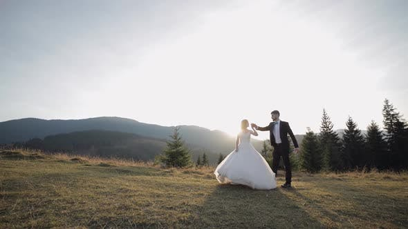 Thumbnail for Newlyweds. Caucasian Groom with Bride Walking on Mountain Slope. Wedding Couple