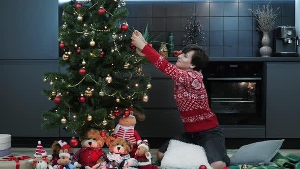 Female is decorating Christmas tree, creating festive mood atmosphere