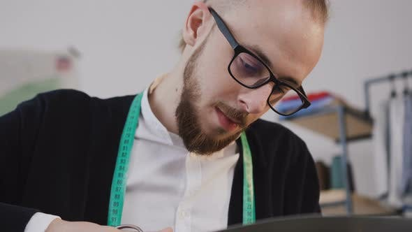 Thumbnail for Young Beared Designer or Tailor in Eyeglasses who Sitting at a Workplase
