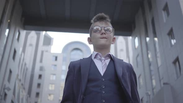 Cover Image for Portrait Cute Well-dressed Boy in Spectacled Standing on the Street Looking in Camera