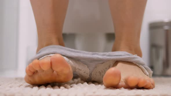 Thumbnail for Low Section Of Woman Sitting On Toilet Bowl In Bathroom.