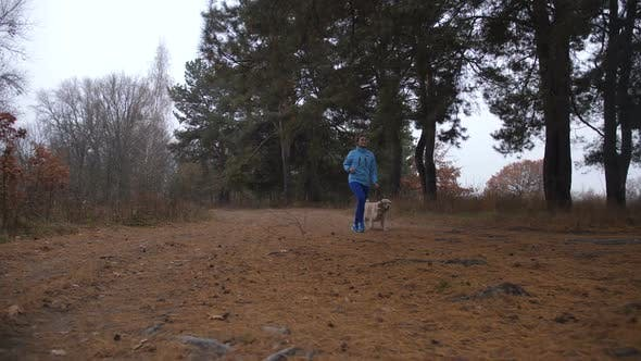 Thumbnail for Sporty Woman Jogging with Dog in Autumn Forest