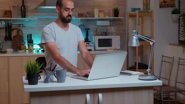 Freelancer Man Streching Neck While Working on Laptop