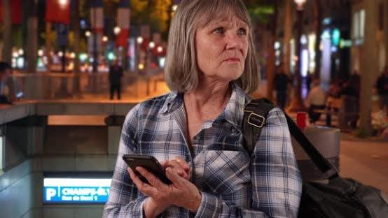 Verwirrte Senior Frau mit Smartphone-Gerät für die Navigation auf Champs-Elysees