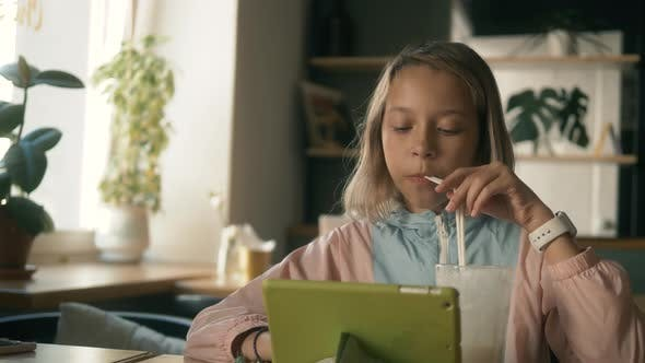 Thumbnail for Cute Kid Girl Using Tablet Computer, Young Teenage Child Doing Homework on Digital Tablet Drink