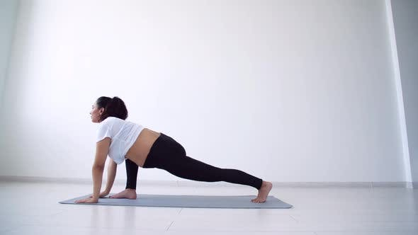 Health Concept. Young Pregnant Woman Does Yoga Exercise in the White Room