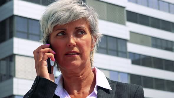 Thumbnail for Business Middle Age Woman Calls with the Smartphone - Company Building in the Background - Closeup