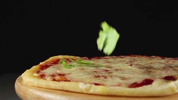 Thumbnail for Basil Slices Fall On A Rotating Pizza On A Black Background