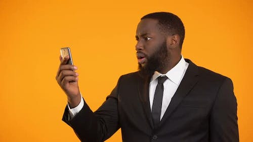 Surprised Afro-American Businessman Satisfied With Mobile Application, Tools