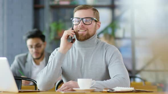 Cover Image for Redhead Businessman Chatting on Mobile Phone in Coffeeshop