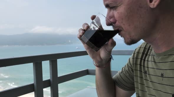 Caucasian Man Drinking Coffee at Balcony with Amazing View of Sea and Mountain