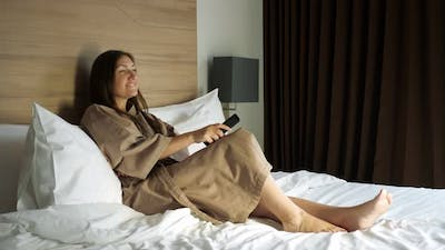 Lady in Bathrobe with Remote Control Watches TV in Hotel