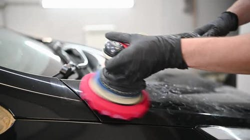 Car Detailing  Hands with Orbital Polisher in Auto Repair Shop in Slow Motion