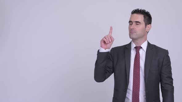 Thumbnail for Handsome Businessman Thinking While Pointing Up