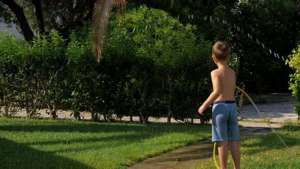 Thumbnail for Kid Playing with Hose When Watering Grass
