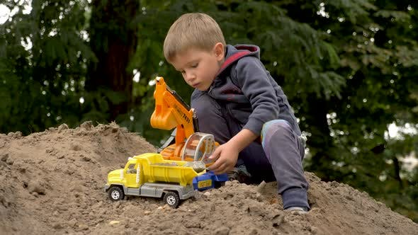 Cover Image for Child Playing Excavator and Dump Truck in Park, Outdoor. Little Builder Loads Sand, Soil, Ground on