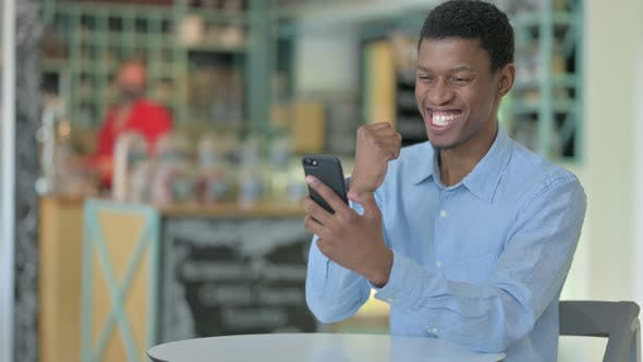 Thumbnail for Ambitious Young African Man Celebrating Success on Smart Phone