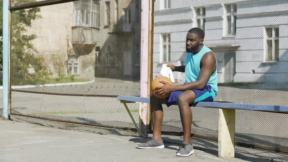 Thumbnail for Sad Afro-American male sitting on the bench and playing ball, loneliness
