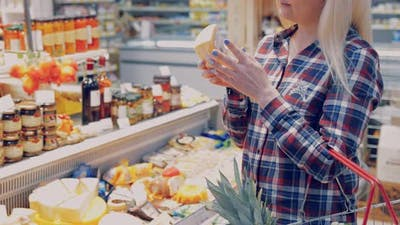 Woman Chooses Cheese in a Supermarket