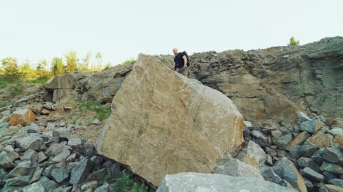 brave traveler is standing on top of a huge rock with his hands raised
