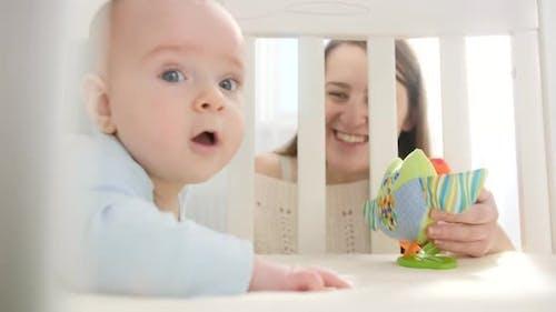 Petit bébé ramper dans le berceau et atteindre pour jouet coloré