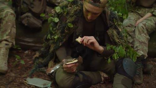 Servicemen Resting in Halt Preparing MRE Rations Eating in Forest