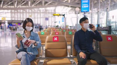 Social distancing, two people wearing face mask sit keeping distance away from each other in airport