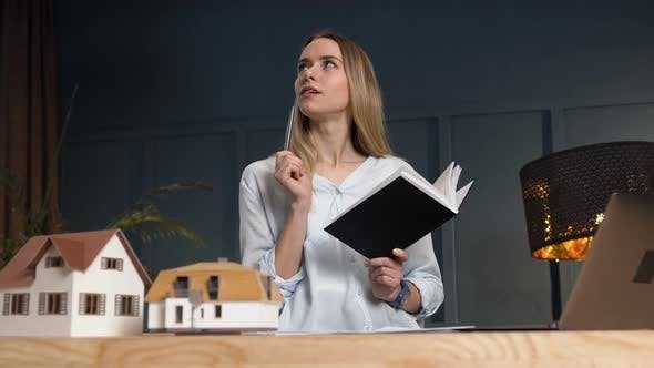 Thumbnail for Thoughtful Female Realtor with Notebook in the Hands During Work in the Office