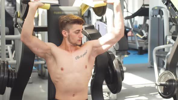 Thumbnail for Young Athlete Trains in the Gym. Bodybuilder Pumping Up Upper Body Muscules.