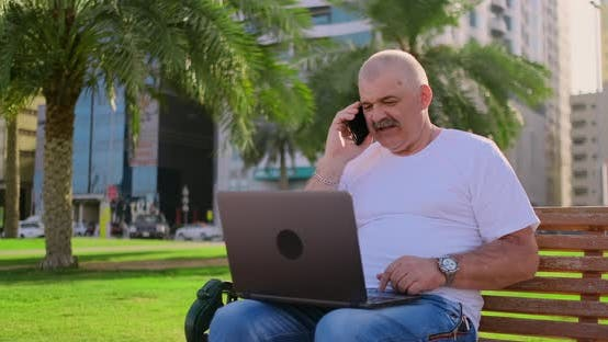 Cover Image for Senior Man Sitting in Park with Laptop in Summer and Chatting