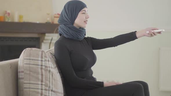 Schöne erfolgreiche selbstbewusste junge muslimische Frau mit der Fernbedienung zum Einschalten des Fernsehers Tragen