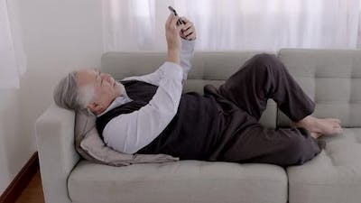 An Asian Elderly video call with smartphone on the sofa on a relaxing day.