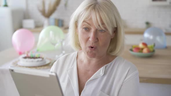 Thumbnail for Positive Mature Woman Getting Surprising News From the Tablet and Smiling