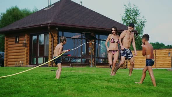 Cover Image for Family in the Backyard of a Country House in the Summer Relax Playing with Water and Hosing