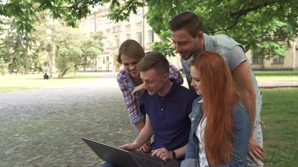 Thumbnail for Four Students Laugh at What They See on Laptop on Campus