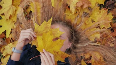 Young Happy Girl Lies in Autumn Leaves and Poses with Maples Leaves