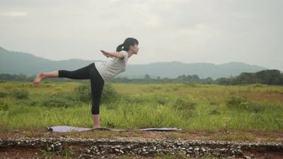 Beautiful young Asian woman performing a spiritual yoga pose on the beautiful landscape.