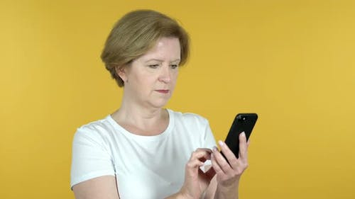Old Woman Browsing Smartphone Isolated on Yellow Background