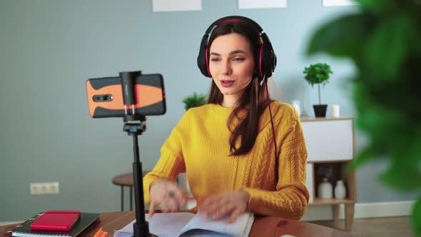 Glücklicher junger Lehrer für Kopfhörer kommuniziert per Videoanruf mit Handy