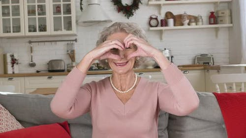 Pensioner with Short Grey Haircut Holds Hands in Heart Shape