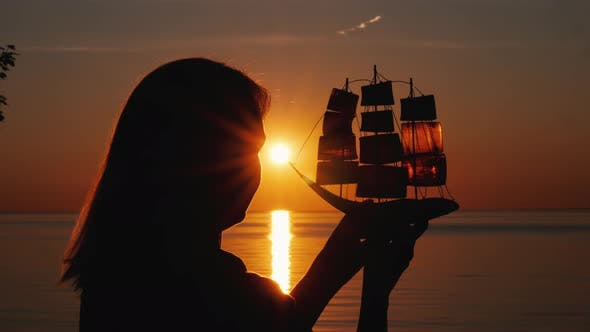 Thumbnail for A Woman Stands By the Sea at Sunset, Holds in Her Hands a Model of a Sailing Ship