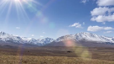 Timelapse of Sun Movement on Crystal Clear Sky with Clouds Over Snow Mountain Top