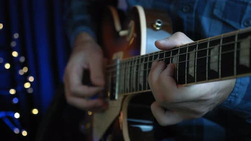Man is playing on electric guitar