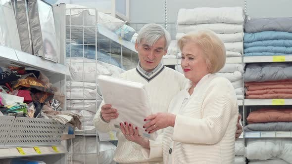 Thumbnail for Lovely Senior Couple Shopping for Bed Sheets at Furniture Store