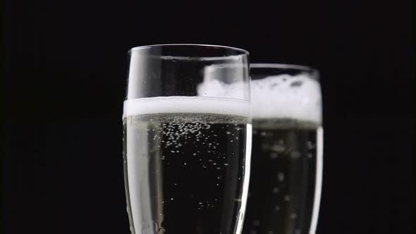 Thumbnail for Gefüllt mit zwei Gläsern Champagner mit weißen Blasen auf schwarzem Hintergrund. Nahaufnahme