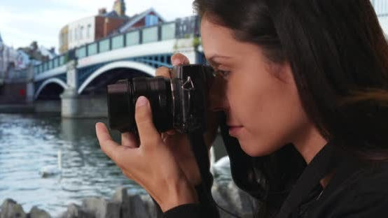 Thumbnail for Millennial woman in England takes scene photo of swans by Windsor Town Bridge