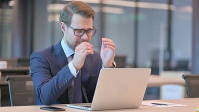 Businessman with Laptop having Headache
