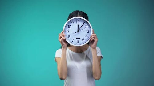 Woman Holding Big Clock Before Her Face, Time Management and Routine, Deadline
