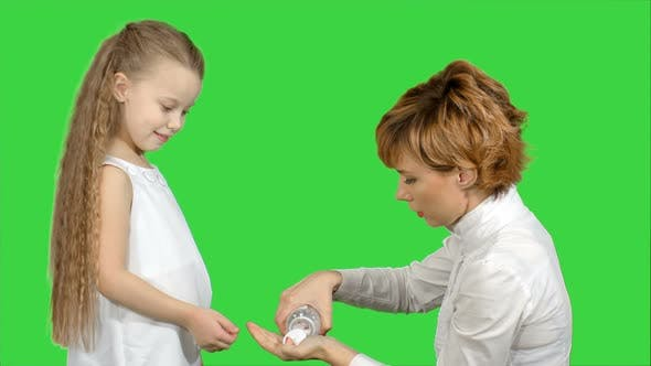 Thumbnail for Mother Giving Her Daughter Medicine on a Green Screen, Chroma Key