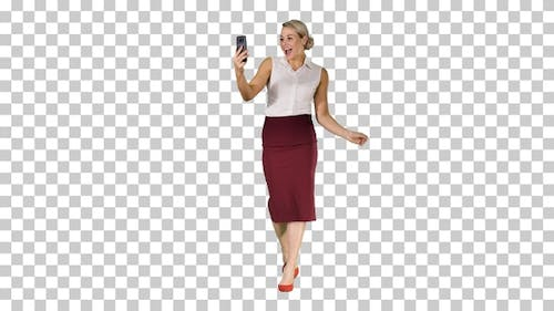Walking woman making a video call using smart phone, Alpha Channel
